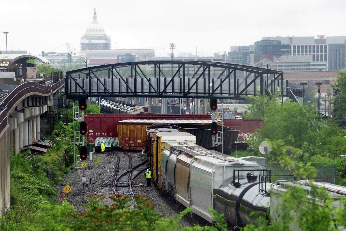 Emergency personnel work at the scene after a CSX freight train derailed, spilling hazardous material, in Washington on Sunday, May 1, 2016. The Capitol is seen in the background. (AP Photo/Cliff Owen) ORG XMIT: DCCO101