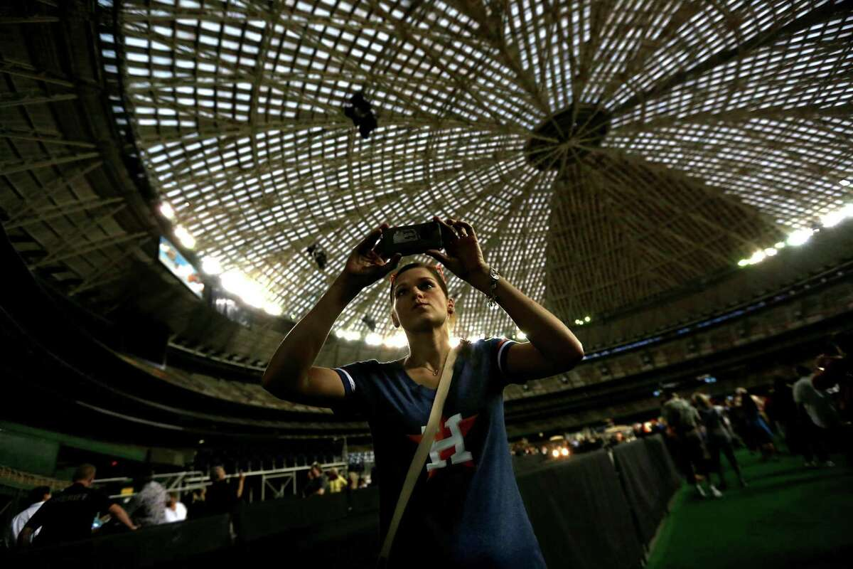 Rebecca Smith, of Conroe, videos the inside of the Astrodome during the 50th anniversary of the opening of the stadium last April. Two Rice graduates say the Dome could be the backdrop for a light show by next year's Super Bowl.