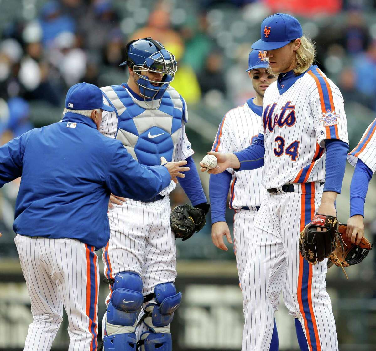 New York Mets starting pitcher Noah Syndergaard, right, leaves a baseball game during the sixth inning against the San Francisco Giants, Sunday, May 1, 2016 in New York. (AP Photo/Seth Wenig) ORG XMIT: NYSW114