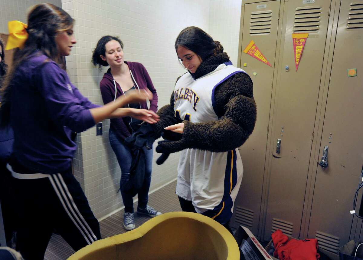 University at Albany cheerleader, Jasmine Noonan, left, a sophomore from Poughkeepsie helps freshman Carolyn Solimine from Mamaroneck get into the Damien the Dane mascot outfit as sophomore MaryKate Montemagno, background, from Sayville, watches on Sunday, May 1, 2016, in Albany, N.Y. Noonan and Montemagno showed up for tryouts to be the mascot for next year. (Paul Buckowski / Times Union)