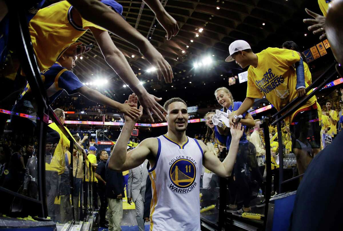 Golden State Warriors' Klay Thompson (11) is high-fived by fans as he walks off the court after a 118-106 win over the Portland Trail Blazers during Game 1 of a second-round NBA basketball playoff series, Sunday, May 1, 2016, in Oakland, Calif. (AP Photo/Marcio Jose Sanchez) ORG XMIT: OAS210