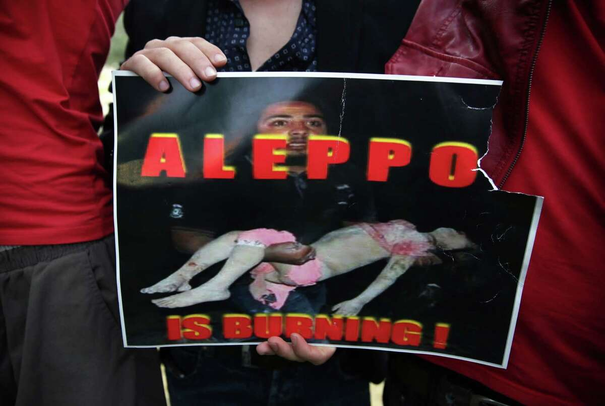 A Syrian man holds a sign during a protest in front of the United Nations headquarters in Beirut, Lebanon, Sunday, May 1, 2016, against Syrian President Bashar Assad's military operations in areas held by insurgents around the country, mostly in the northern city of Aleppo that has been the main point of violence. (AP Photo/Bilal Hussein) ORG XMIT: XBH115