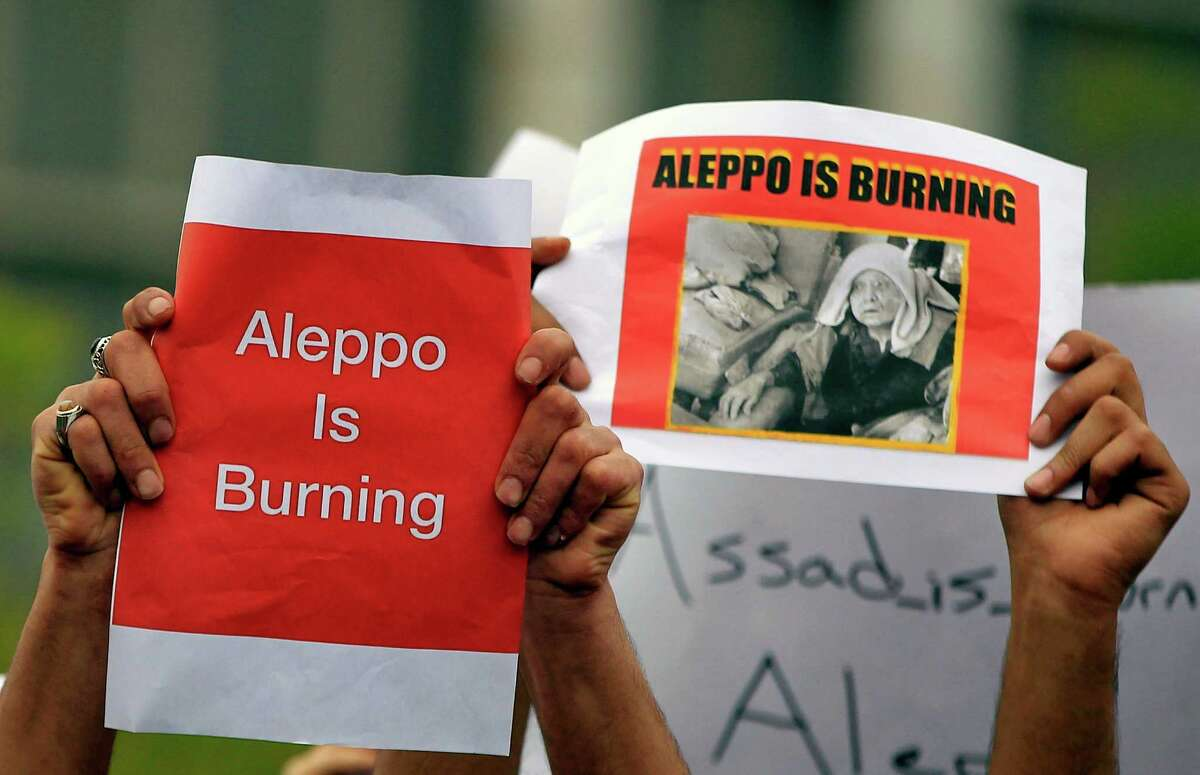 Protesters hold up placards during a protest in front of the United Nations Headquarters in Beirut, Lebanon, Sunday, May 1, 2016, against Syrian President Bashar Assad's military operations in areas held by insurgents around the country, mostly in the northern city of Aleppo that has been the main point of violence. (AP Photo/Bilal Hussein) ORG XMIT: XBH112