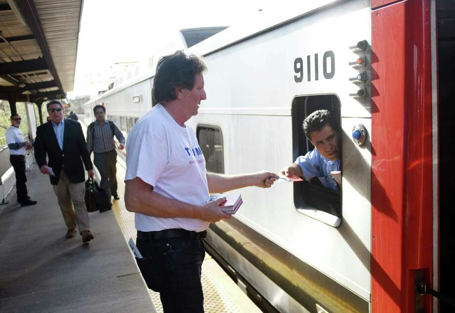 Donald Trump supporter Joe Visconti  hands a leaflet to a conductor at the Greenwich station last month. Photo: Tyler Sizemore / Hearst Connecticut Media / Greenwich Time
