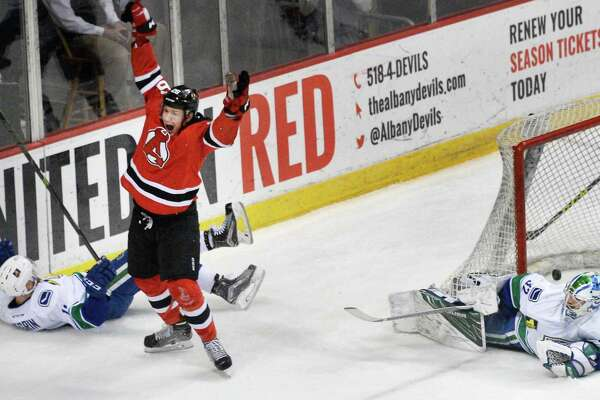 Albany Devils' #26 Ben Thomson celebrates his goal against  Utica Comets goalie Richard Bachman, right, during Game 2 of their playoff series sat the Times Union Center Saturday April 23, 2016 in Albany, NY.  (John Carl D'Annibale / Times Union)
