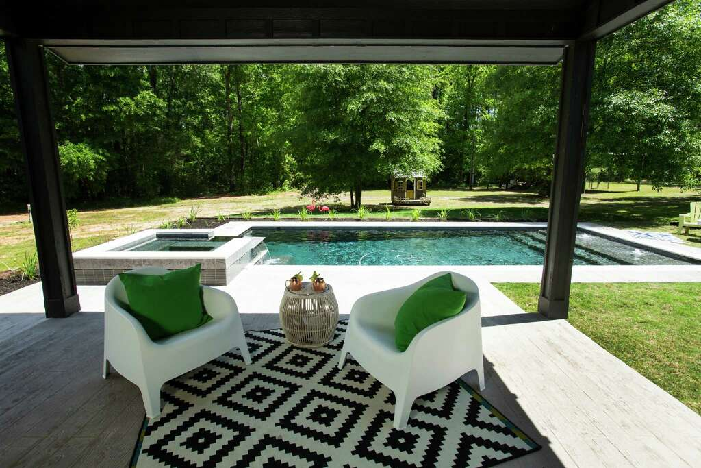 just off the kitchen and dining area a covered deck leads to the pool behind - Home Design Houston