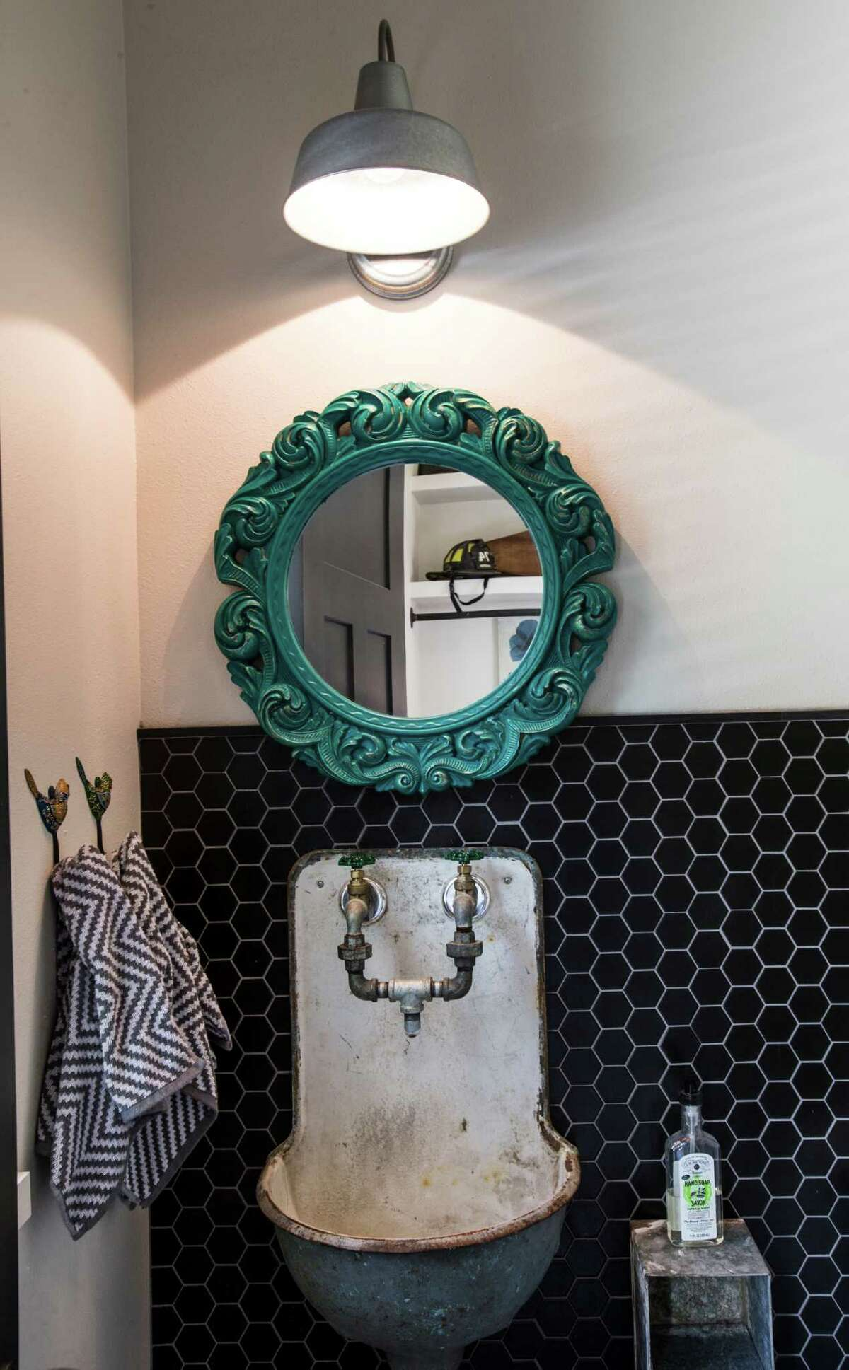 ANTIQUES: An antique sink and mirror play off sleek black tiles in this powder room.