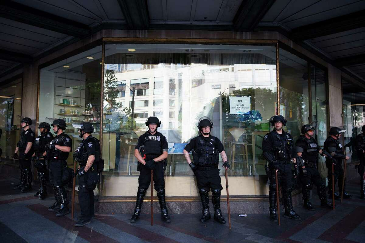 Seattle police officers stand guard in front of a Macy's as demonstrators gather at the Westlake Center across the street for the annual anti-capitalist May Day march on Sunday, May 1, 2016.