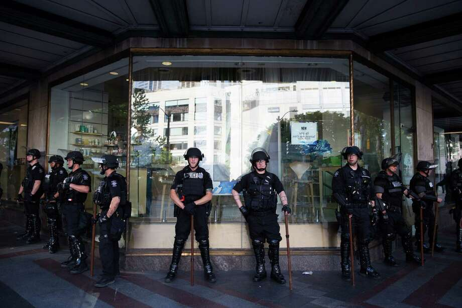 Seattle police officers  stand guard in front of a Macy's as demonstrators gather at the Westlake Center across the street for the annual anti-capitalist May Day march on Sunday, May 1, 2016. Photo: GRANT HINDSLEY, SEATTLEPI.COM / SEATTLEPI.COM