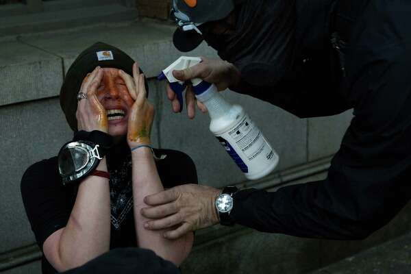 A May Day demonstrators has milk sprayed in her eyes to sooth the pain after receiving a direct blast of pepper spray during the annual anti-capitalist May Day march, Sunday, May 1, 2016.