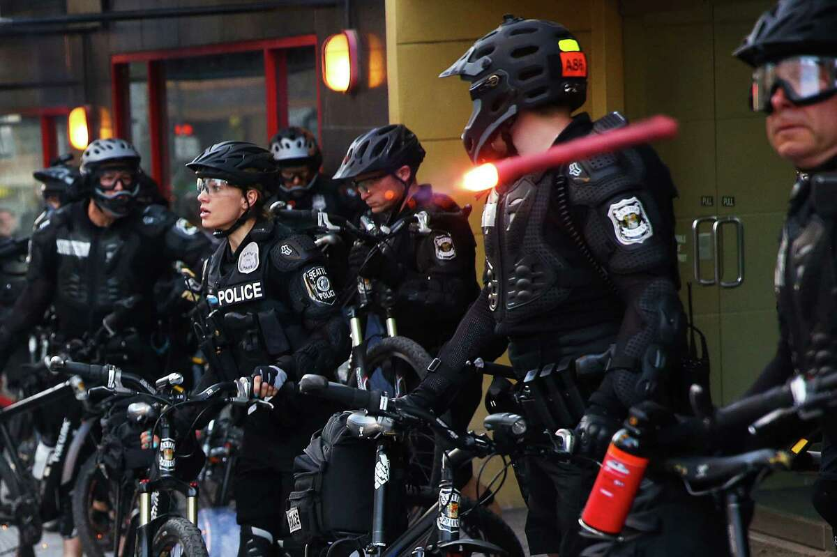 A lit flare is thrown at a line of Seattle police officers by a demonstrator during the annual anti-capitalist May Day march through downtown Seattle, Sunday, May 1, 2016.