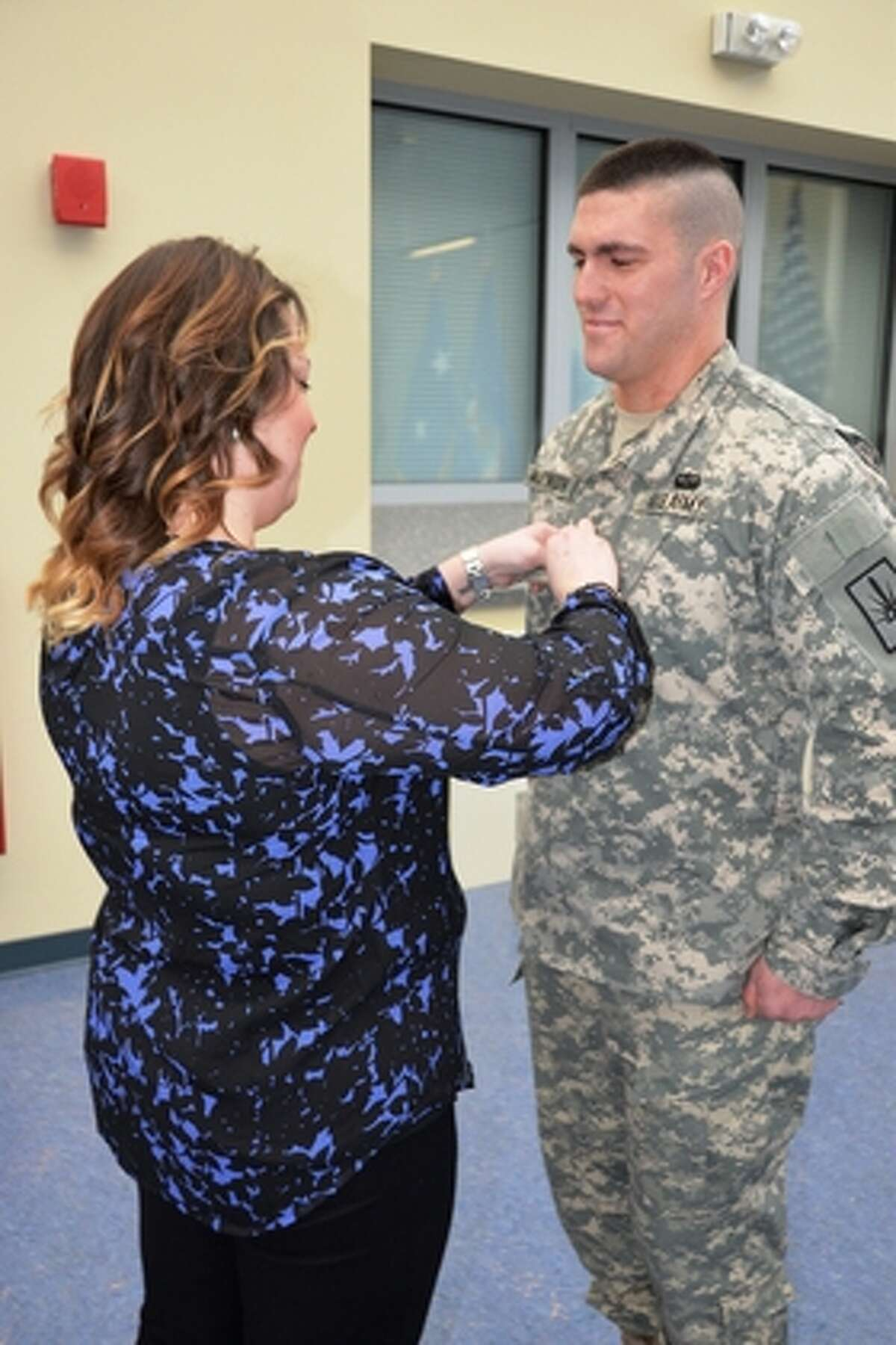 New York Army National Guard Wife Ashley Martinsen places new sergeant first class rank insignias on David Martinsen during promotion ceremony at New York Army National Guard Headquarters in Latham.