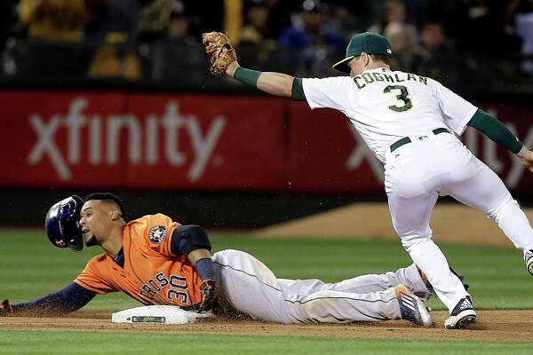 Houston Astros' Carlos Gomez, left, is tagged out at third base by Oakland Athletics' Chris Coghlan (3) in the ninth inning of a baseball game Friday, April 29, 2016, in Oakland, Calif. (AP Photo/Ben Margot)