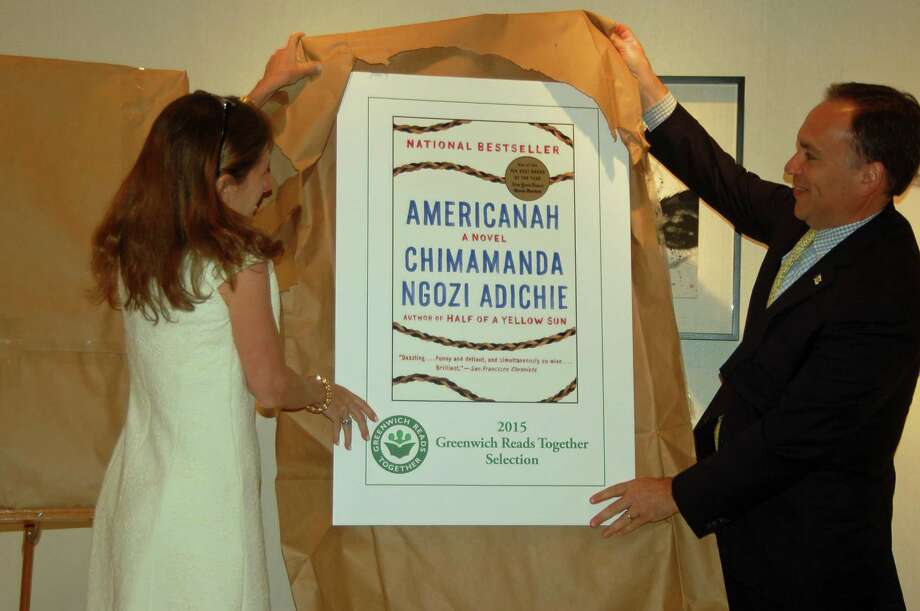 Haley Rockwell Elmlinger, head of Greenwich Library's Board of Trustees, and First Selectman Peter Tesei tear the wrapping off a poster of the cover to Americanah by Chimamanda Ngozi Adichie, last year's choice for Greenwich Reads Together. The choice for 2016 will be revealed on Wednesday morning. Photo: Ken Borsuk / Ken Borsuk / Greenwich Time