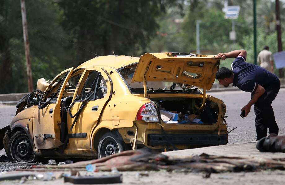 A man examines the damage following a car bombing that targeted Shiite pilgrims in Baghdad. The attack came a day after two car bombs in the southern city of Samawah killed 31 people. Photo: HAIDAR MOHAMMED ALI, AFP/Getty Images