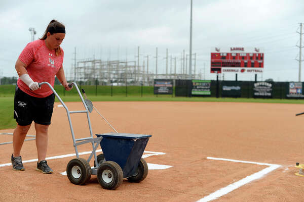 Brittany Baker, assistant softball coach at Lamar University, lays the chalk lines for the batter's box before the Lady Cardinals' game against McNeese State on Friday.  Photo taken Friday 4/29/16 Ryan Pelham/The Enterprise
