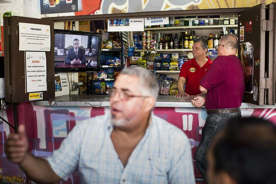 """A bartender and customers watch Alejandro Garcia Padilla, governor of Puerto Rico, discuss the island territory's default on bond payments. """"Our worst enemy at the moment is politics,"""" Padilla said. Photo: Erika P. Rodriguez, Bloomberg"""