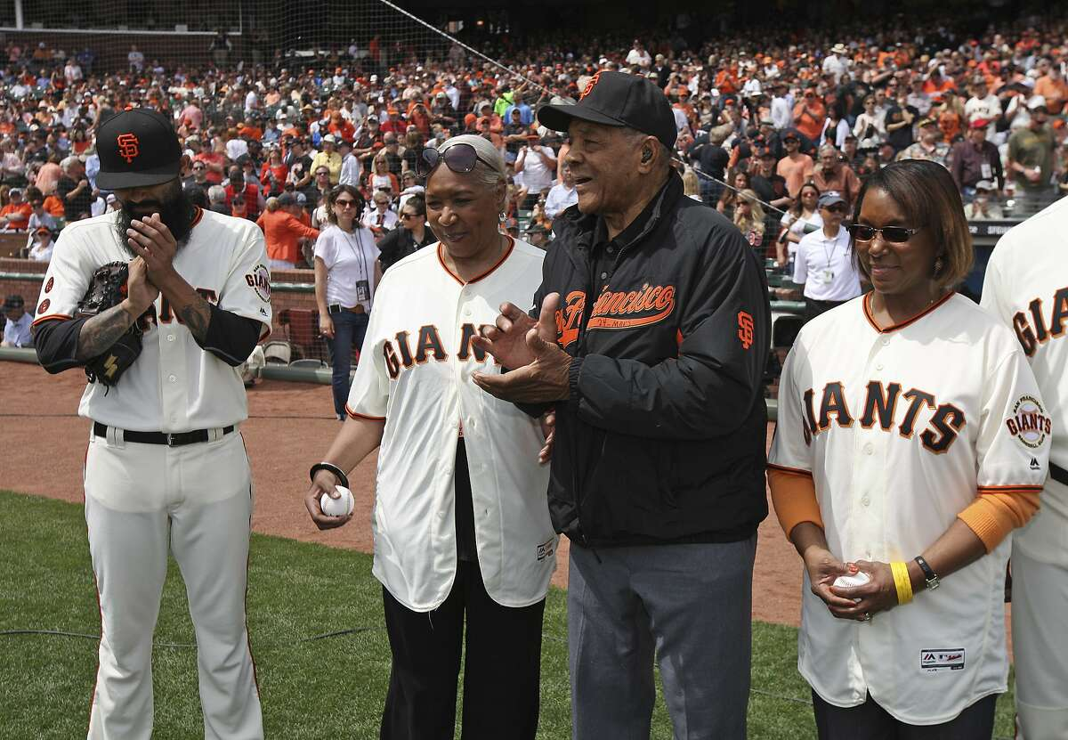 Hall of Famer Willie Mays stands with Pamela Irvin Fields, second from left, and Patricia Irvin Gordon, right, the daughters of Hall of Famer Monte Irvin, before the start of an opening day baseball game between the San Francisco Giants and Los Angeles Dodgers Thursday, April 7, 2016, in San Francisco. At left is Giants pitcher Sergio Romo. The daughters of Irvin, who died in January, threw out the ceremonial first pitch. (Jason Watson/POOL via AP)