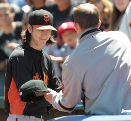 Giants' pitcher Tim Lincecum, left, signs autographs for fans at the Coliseum in Oakland, Calif. on Sunday, June 24, 2012.