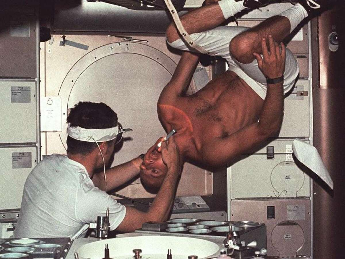 """Astronaut Joseph P. Kerwin, science pilot for the first manned Skylab mission and a medical doctor, conducts a physical exam for Astronaut Charles """"Pete"""" Conrad, Jr., the Skylab 2 mission commander. Conrad almost literally stands on his head in the weightlessness of space with only a restraint around his left leg holding in position. The Skylab crews added volumes to our knowledge about how humans live and work in space. Image Credit: NASA"""