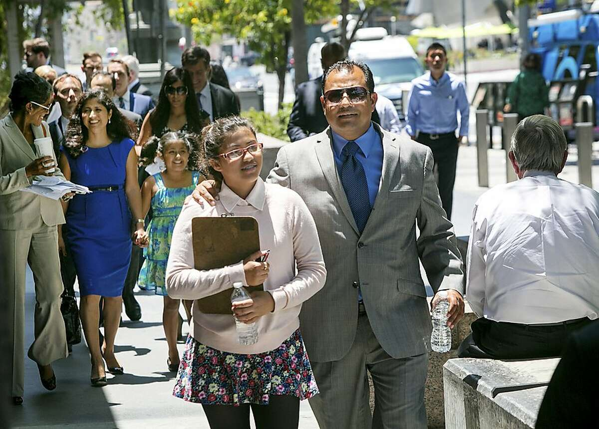 Plaintiff Julia Macias, one of nine plaintiffs in the Vergara v. State of California case, walks to a news conference with her father Joe Macias outside Los Angeles Superior Court following a judge's ruling on the case, June 10, 2014. The judge ruled that teacher tenure laws are unconstitutional, a decision that stands as a major blow against teachers' unions and could trigger a slew of legal fights in other states. (Monica Almeida/The New York Times)