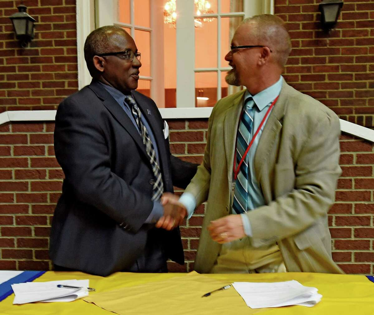 Schenectady County Community College(SCCC) president Dr. Steady H. Moono, left shakes hands after signing a memorandum of agreement with Niskayuna School Superintendent Dr. Cosimo Tangorra jr. Monday May 2, 2016 which will allow international students at the high school to continue their education at SCCC in Schenectady, N.Y. The agreement is the first of it's kind in the State. (Skip Dickstein/Times Union)