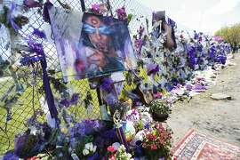 A painting of Prince is displayed on an easel at the flower-covered fence at Paisley Park Studios Monday, May 2, 2016, in Chanhassen, Minn. where pop rock singer Prince died on April 21. A Carver County judge on Monday confirmed the appointment of a special administrator to oversee the settlement of Prince's estate. (AP Photo/Jim Mone)