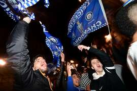 Leicester City fans wave flags as they celebrates their team becoming the English Premier League football champions in central Leicester, eastern England, on May 2, 2016 after Chelsea held Tottenham Hotspur to a 2-2 draw in the English Premier League match.  Leicester City completed their fairytale quest for the Premier League title on May 2 after Eden Hazard's stunning late goal earned Chelsea a 2-2 draw with second-place Tottenham Hotspur.  / AFP PHOTO / LEON NEALLEON NEAL/AFP/Getty Images