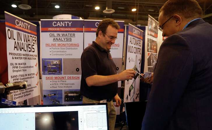 Tod Canty, Jr. chats with a customer in his booth at the 2016 Offshore Technology Conference at NRG Park, Monday, May 2, 2016, in Houston. Canty was unable to rent a car at a reasonable rate because of the recent flooding in the area.  ( Karen Warren  / Houston Chronicle )