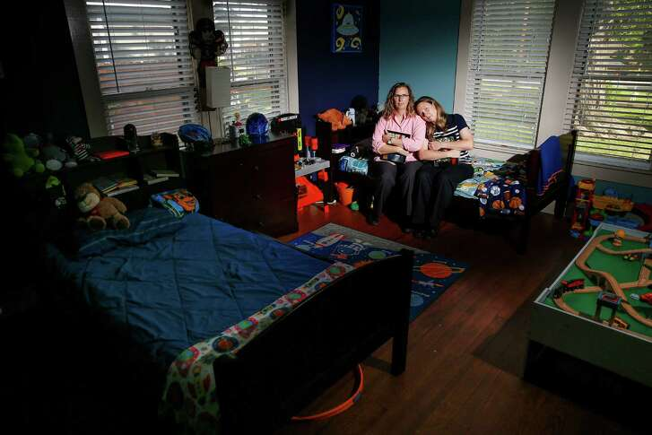 Holding pictures of their two foster kids, parents Angela Sugarek, left, and Carol Jeffery sit on the bed of the younger of their two foster children Wednesday, April 27, 2016 in Houston. The couple had the two bothers, ages three and four, taken away from them by Child Protective Services after reporting that they believed the younger child was being abused by an older brother. ( Michael Ciaglo / Houston Chronicle )