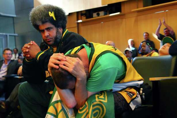 """Seattle SuperSonics fans Kris """"Sonics Guy"""" Brannon, left, and Kenneth Knutsen react to the Seattle City Council's 5-4 no vote against a """"street vacation"""" vacating stretch of road where investor Chris Hansen hopes to eventually build an arena that could house an NBA and NHL team."""