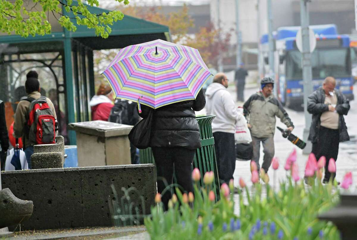 A woman uses an umbrella in the rain at a bus stop on Monday, May 2, 2016. in Troy, N.Y. (Lori Van Buren / Times Union)