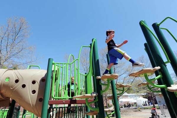 Top right, Alek McMahon, 6, of Darien, enjoys the new playground at North Mianus School in Greenwich on Saturday.