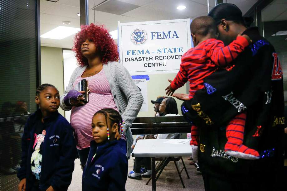 Jennifer Ukeju waits with daughters Satteriyah, 7, left, Shamarriyah, 5, and fiancé Patrick Hill and his son, Levi, 1, for a center to open. Photo: Michael Ciaglo, Staff / © 2016  Houston Chronicle