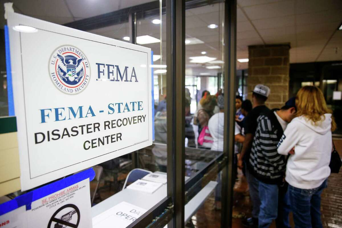 Kiesha James, left, waits in a line with her mother, Shelly Russell, right, and her son, Brandon Beck, 2, for one of four FEMA disaster recovery centers to open Monday in Houston. Officials stressed that residents should register for aid even if they think they don't qualify.