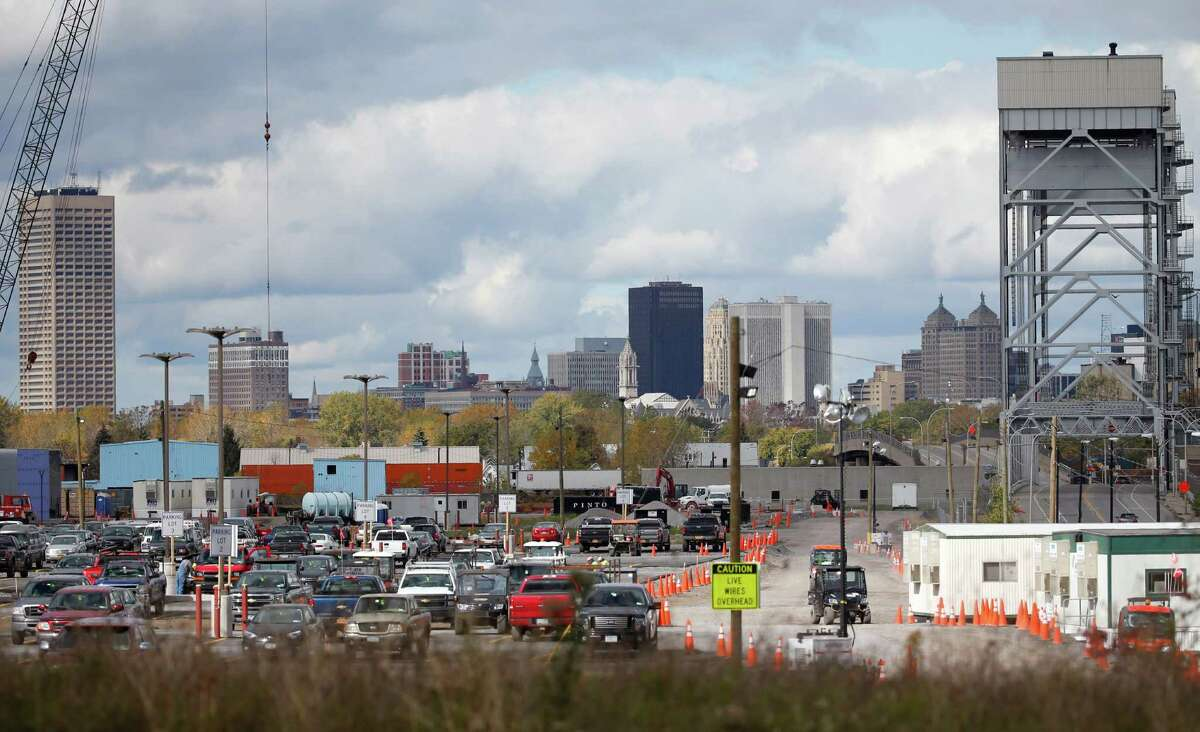 In this Saturday, Oct. 17, 2015 photo, the Buffalo skyline is seen beyond where construction work continues at a high-tech manufacturing site in Buffalo, N.Y. New York is committing $750 million to the factory for Elon Musk's SolarCity in exchange for a promise of 3,000 jobs and a $5 billion investment in manufacturing solar panels. It's a centerpiece of Gov. Andrew Cuomo's