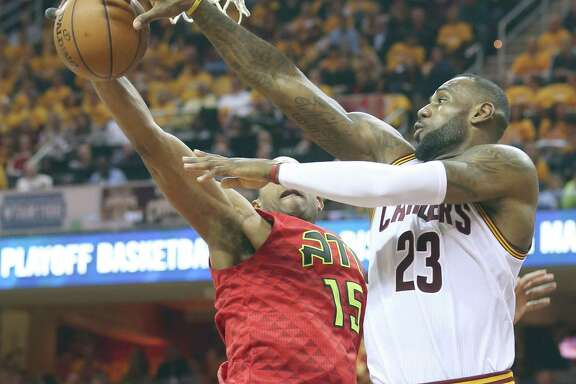 The Cavaliers' LeBron James looks to pass around the Hawks' Al Horford during the second quarter Monday at Quicken Loans Arena.