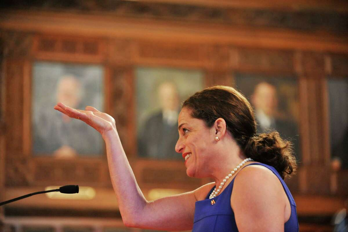 Luisa Kaye, daughter of the late Chief Judge Judith Kaye, gestures up towards the portrait of her mother hanging on the back wall in the New York State Court of Appeals during the annual Law Day on Monday, May 2, 2016, in Albany, N.Y. Luisa Kaye joked that she was going to share some juicy secrets about her mother but said