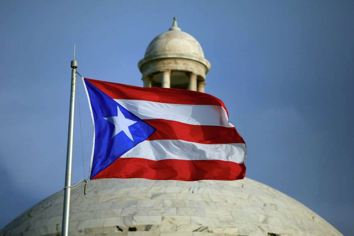 FILE - In this Wednesday, July 29, file 2015 photo, the Puerto Rican flag flies in front of Puerto Rico?'s Capitol as in San Juan, Puerto Rico. Puerto Rico Gov. Alejandro Javier Garcia Padilla said on Sunday, May 1, 2016, that negotiators for the U.S. territory?'s government have failed to reach a last-minute deal to avoid a third default and that he has issued an executive order to withhold payment. (AP Photo/Ricardo Arduengo, File) ORG XMIT: XLAT113