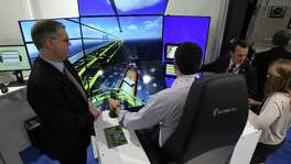 Rolf Lange, left, and Stephan Herentrey, second from right, with Rheinmetall in Germany, talk Monday to Noble Energy's TJ Jacobs, in a crane simulator, and Paige Billings at the Offshore Technology Conference.