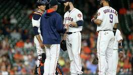 Houston Astros starting pitcher Dallas Keuchel (60) is taken off the mound by Houston Astros manager A.J. Hinch (14) in the top of the fifth inning. Photos of game one between Houston Astros and Minneapolis Twins at Minute Maid Park on   Monday, May 2, 2016, in Houston.