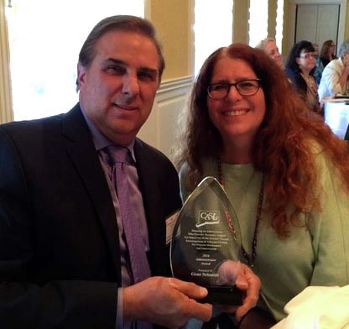 Cos Cob School Principal Gene Schmidt, with Cos Cob media specialist Nancy Shwartz, shows the Administrators Award he won from the Connecticut Association of School Librarians.