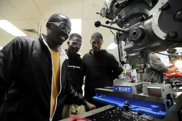 From left, Bassick High School juniors Omar Lukole, 16, Arcadius Takinda, 17, and C.J. Ephraim, 16, use a milling maching to create an L-shaped bracket from a block of aluminum in their manufacturing class at Housatonic Community College in Bridgeport on Thursday. The college has partnered with the Bridgeport high school to allow select students to take classes in the advanced manufacturing program.