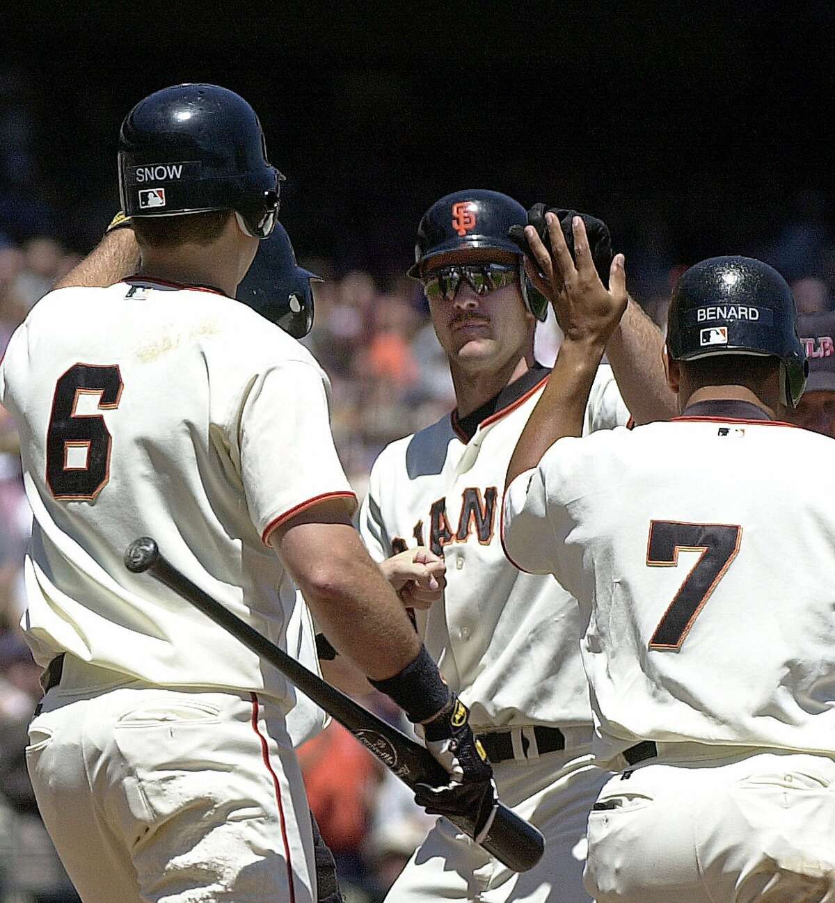 San Francisco Giants' Jeff Kent, center, is welcomed at home plate by teammates J.T. Snow (6) and Marvin Benard (7) after hitting a grandslam off Milwaukee Brewers' Paul Rigdon in the second inning Wednesday, Aug. 9, 2000, at Pacific Bell Park in San Francisco. (AP Photo/Ben Margot)