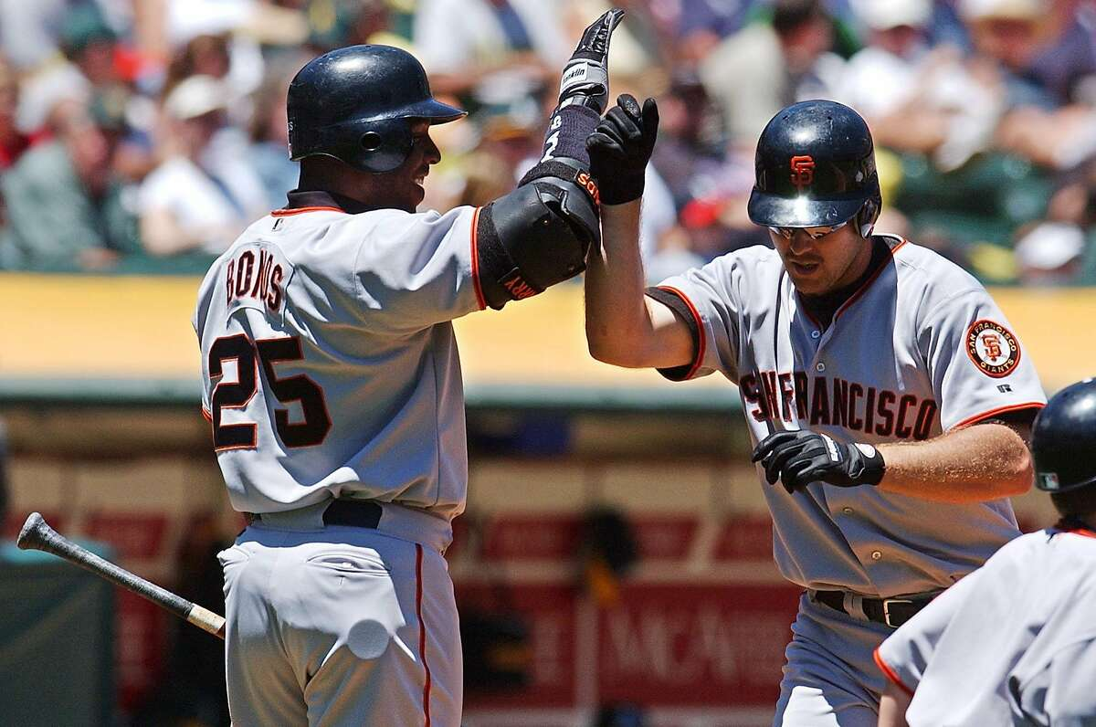 San Francisco Giants' Barry Bonds, left, greets Jeff Kent at home plate after Kent hit a two run home run against the Oakland Athletics during the first inning Saturday, June 29, 2002 in Oakland, Calif. Giants' Rich Aurilia scored on the hit. (AP Photo/Julie Jacobson)