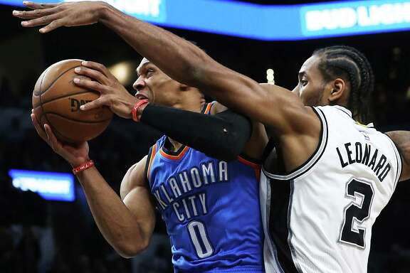 Kawhi Leonard tries to put a stop to the hot shooting Russell Westbrook in the first quarter as the Spurs host the Thunder in game 2 of second round NBA playoff action at the AT&T Center on May 2, 2016.