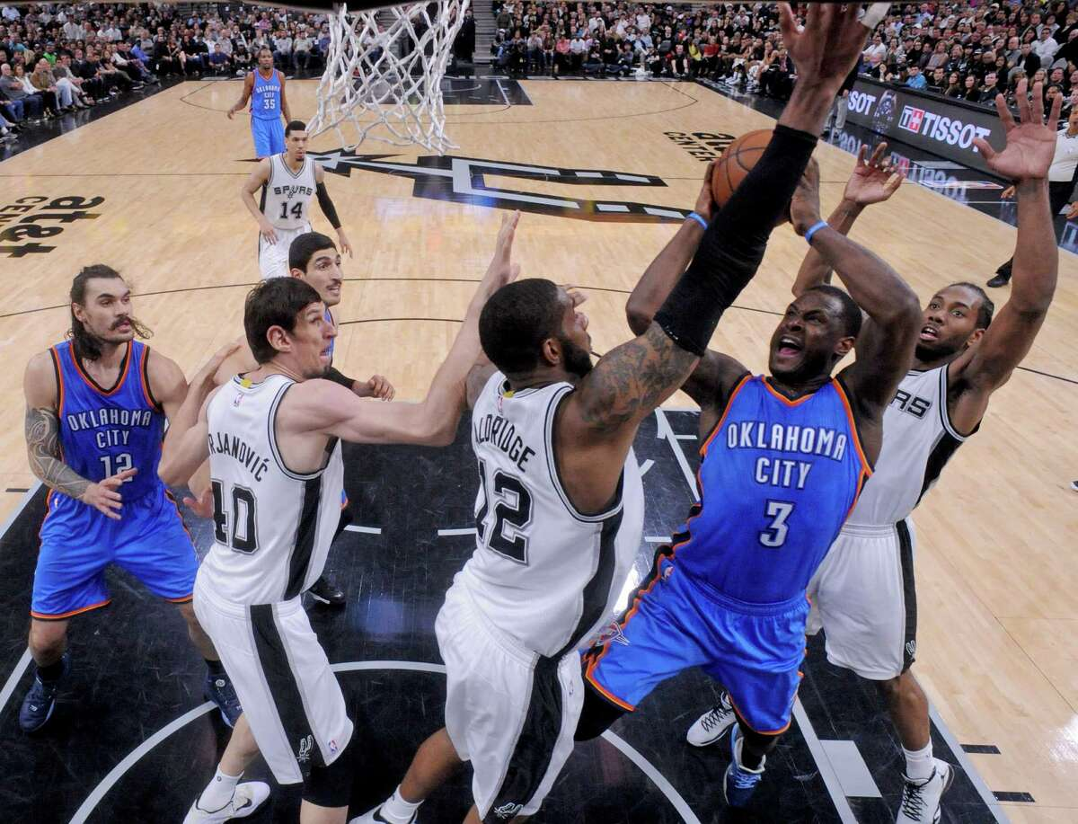 Oklahoma City Thunder's Dion Waiters shoot between San Antonio Spurs' LaMarcus Aldridge (center left) and Kawhi Leonard as Oklahoma City Thunder's Steven Adams and San Antonio Spurs' Boban Marjanovic look on during Game 2 in the Western Conference semifinals Monday May 2, 2016 at the AT&T Center. The Thunder won 98-97.