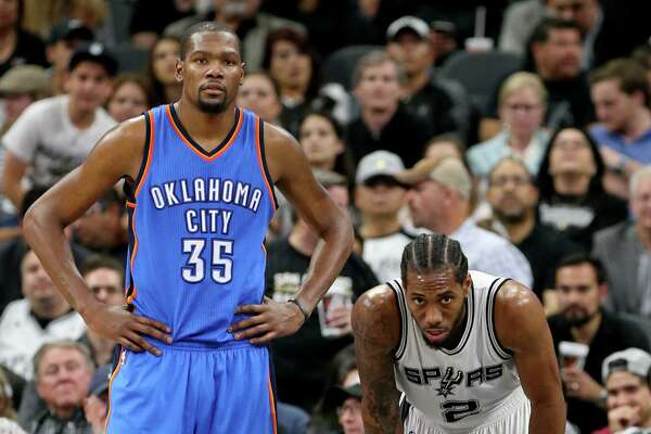 Oklahoma City Thunder's Kevin Durant and San Antonio Spurs' Kawhi Leonard pause during second half action of Game 2 in the Western Conference semifinals Monday May 2, 2016 at the AT&T Center. The Thunder won 98-97.