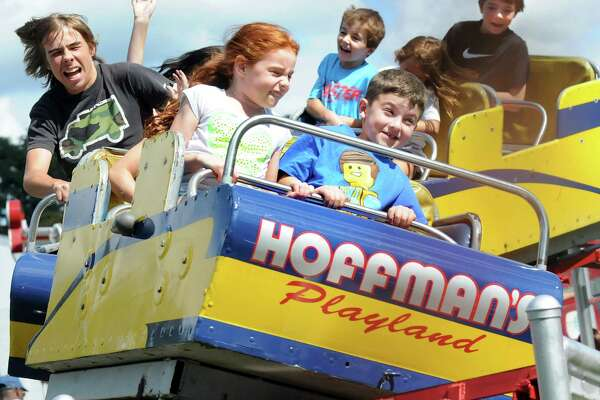 Children and their families scream as they round a curve on the roller coaster on Friday, Aug. 29, 2014, at Hoffman's Playland in Latham N.Y. (Cindy Schultz / Times Union)