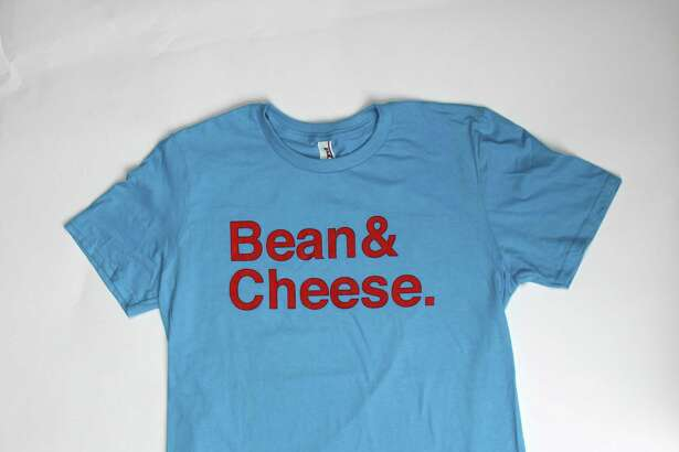 """Bean & Cheese ($24 at barbacoapparel.com, also available at the San Antonio Museum of Art, Leighelena, Roo & Me, and Whole Earth Provision Co.). You know San Antonio won the great taco war with Austin, but did you know it also wins at taco T-shirts? Feast your eyes on the fashions of BarbacoApparel. The aptly named, S.A.-based clothing line serves up taco tees based on Experimental Jetset's famous """"John & Paul & George & Ringo design,"""" with """"Bean & Cheese,"""" """"Carne Guisada,"""" and other texty, er, tasty tacos our state capitol can't get right. For a more picturesque look at tacos on the brain, try BarbacoApparel's Always On My Mind shirt, which features a mustachioed dude with, well, """"tacos"""" on the brain."""